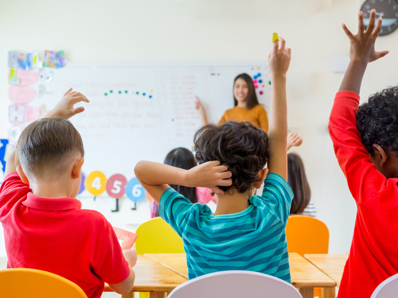 Three boys with their hand up in a classroom with a teacher
