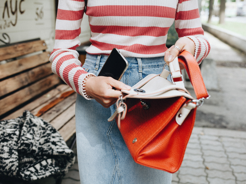 Woman holding a handbag and mobile phone