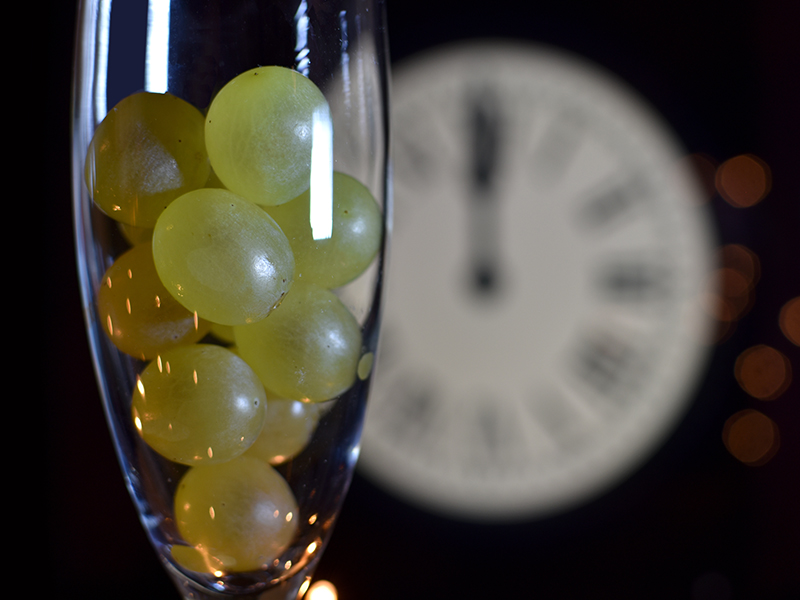 12 grapes placed in glass in front of a classic clock