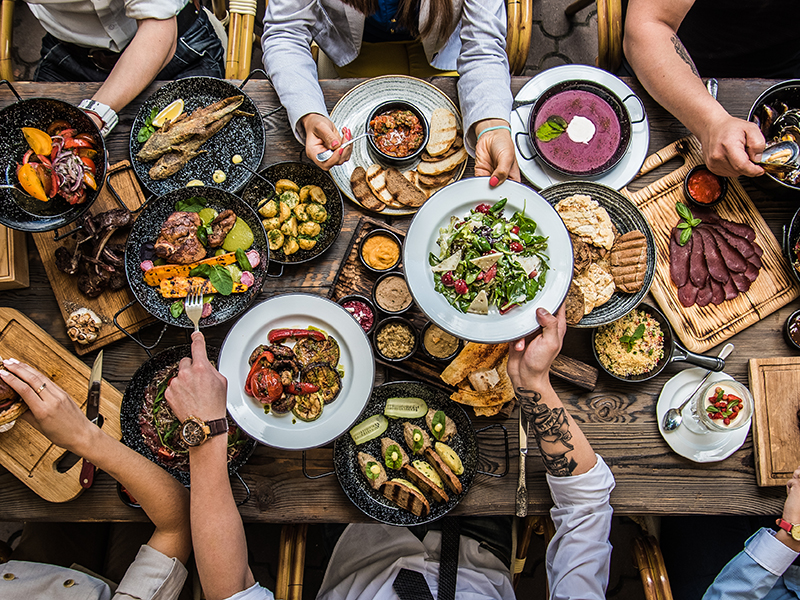 Top view image of friends gathered at a dinner table with lots of food