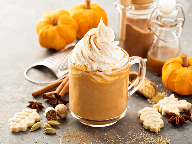 A homemade pumpkin spice latte surrounded with autumn leave cookies and scattered all spice.